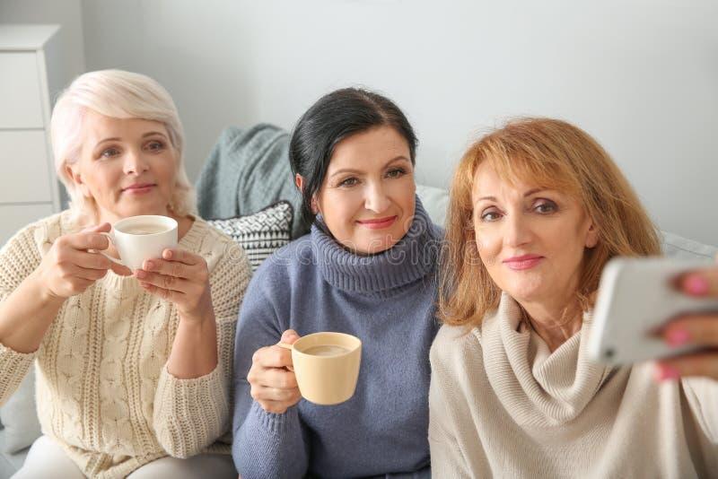 Härlig mogen kvinna som dricker kaffe, medan ta selfie hemma royaltyfria foton