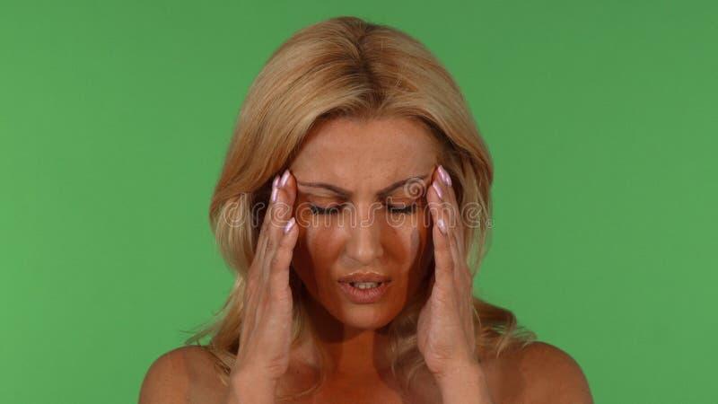Härlig mogen kvinna som har huvudvärk royaltyfri foto