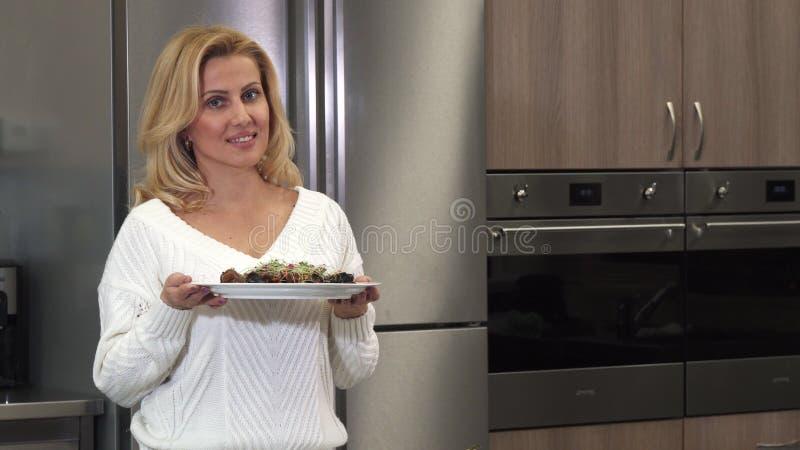 Härlig mogen kvinna som ler till kameran som poserar med en maträtt, når att ha lagat mat royaltyfria bilder