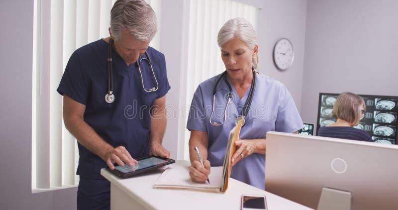 Härlig mogen tålmodig mapp för sjuksköterskahandstilanmärkningar in - med den manliga kollegan arkivbild