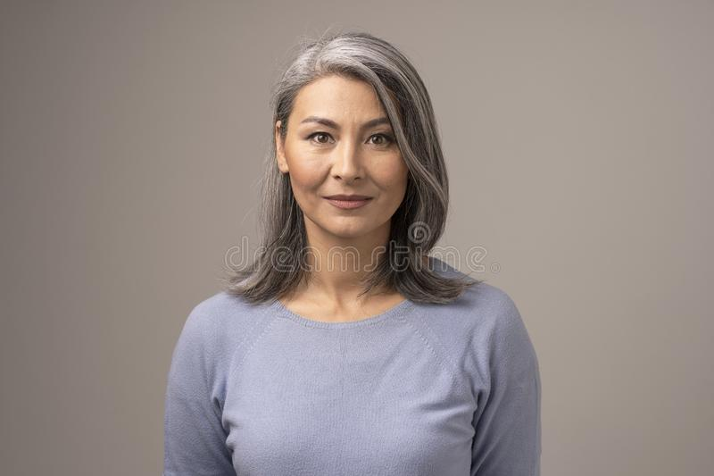 Härlig mongolisk kvinna med Gray Hair på en Gray Background royaltyfria foton