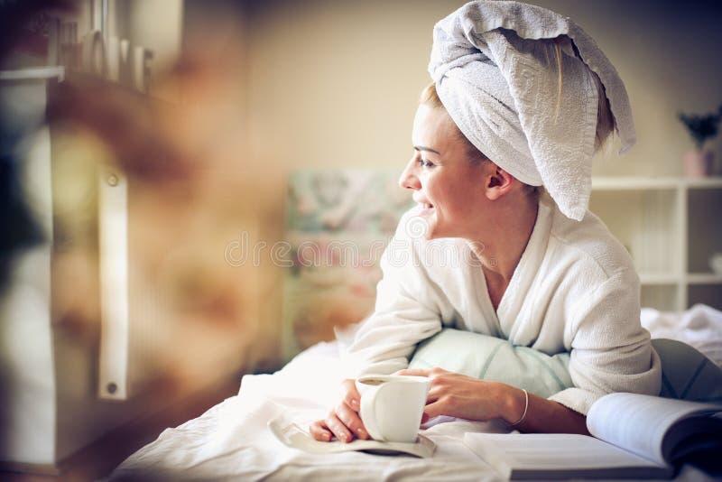 Härlig morgon Mellersta ålderkvinna som dricker kaffe i hennes säng royaltyfri fotografi