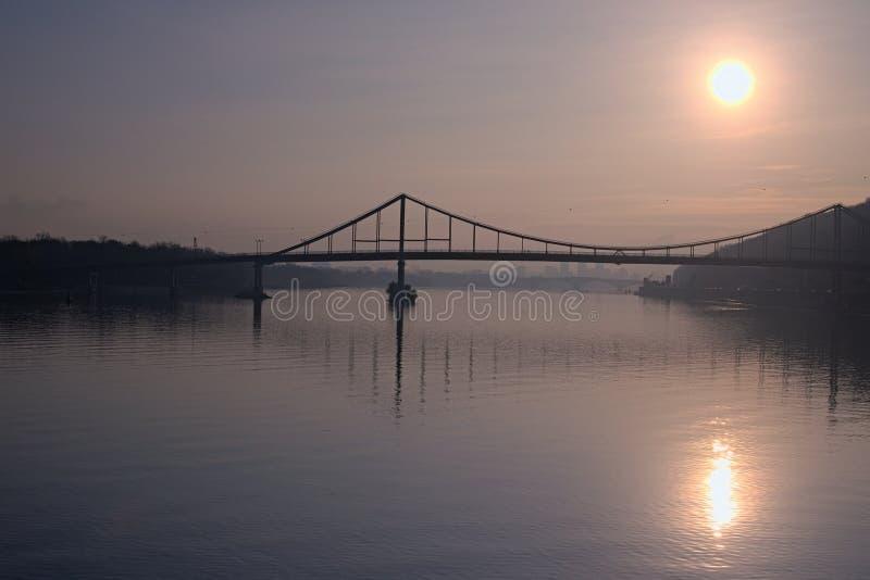 Härlig morgoncityscape Solen reflekteras i vatten konturer av hus som döljas i ogenomskinligheten Fot- bro till Truen royaltyfri fotografi