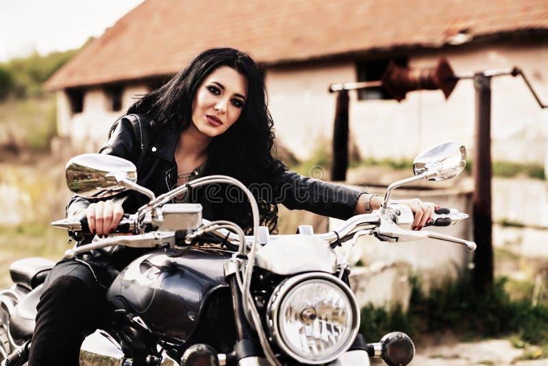 Härlig motorcykelbrunettkvinna med en klassisk motorcykel c arkivfoton