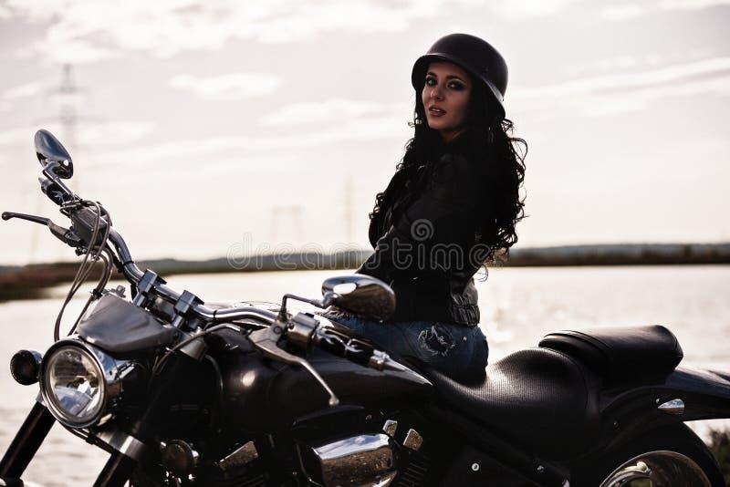 Härlig motorcykelbrunettkvinna med en klassisk motorcykel c arkivbilder