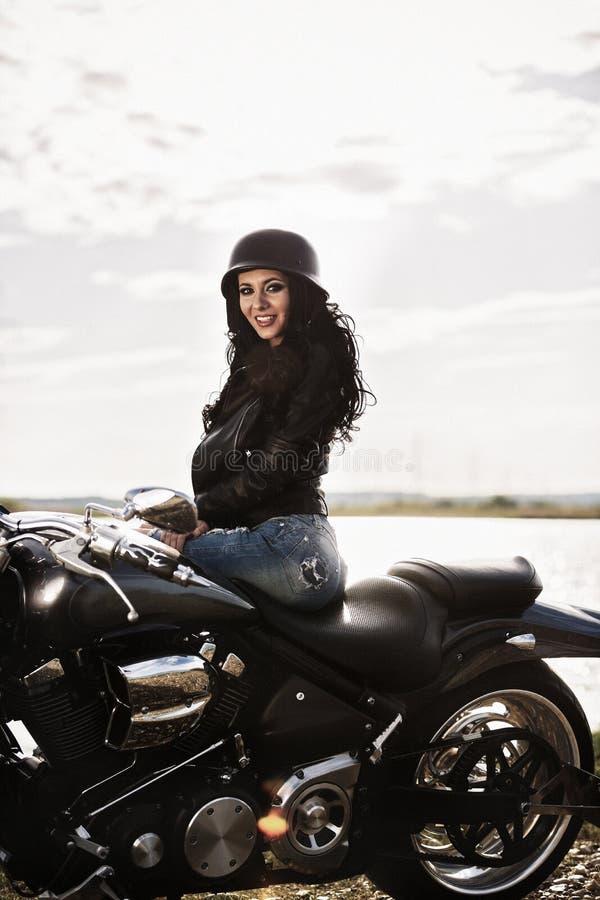 Härlig motorcykelbrunettkvinna med en klassisk motorcykel c arkivbild