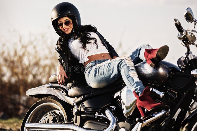Härlig motorcykelbrunettkvinna med en klassisk motorcykel c royaltyfria foton