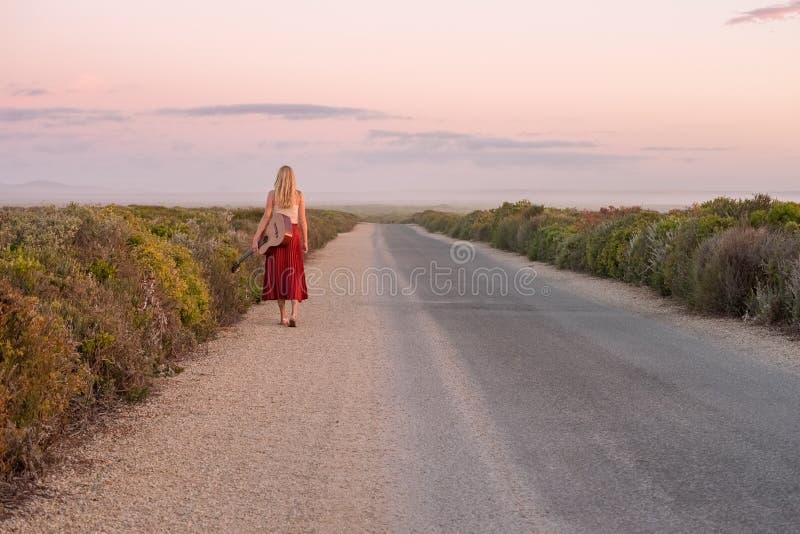 Härlig musikerflicka som går ner en avskild väg på solnedgången med hennes gitarr arkivfoto