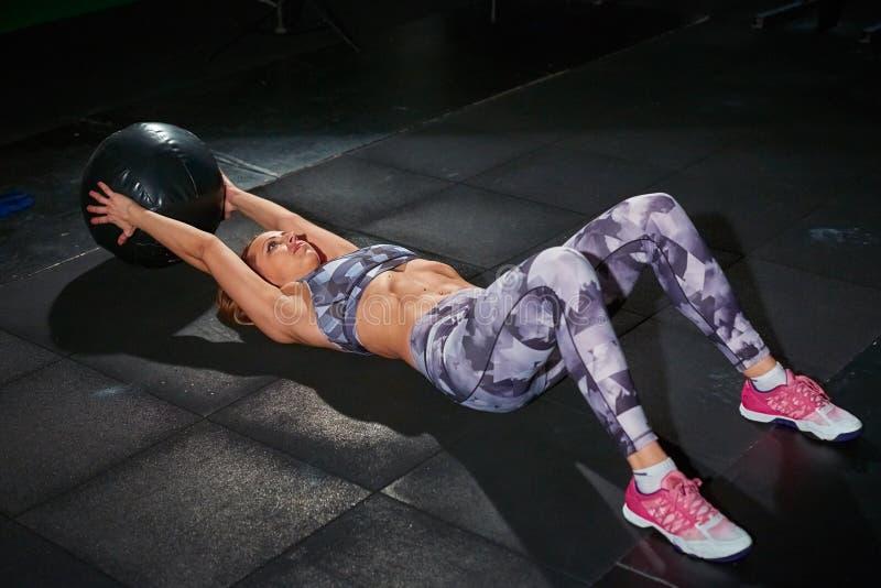 Härlig muskulös passformkvinna med crossfitbollen, grå tegelstenvägg i bakgrunden Arg passform royaltyfria bilder