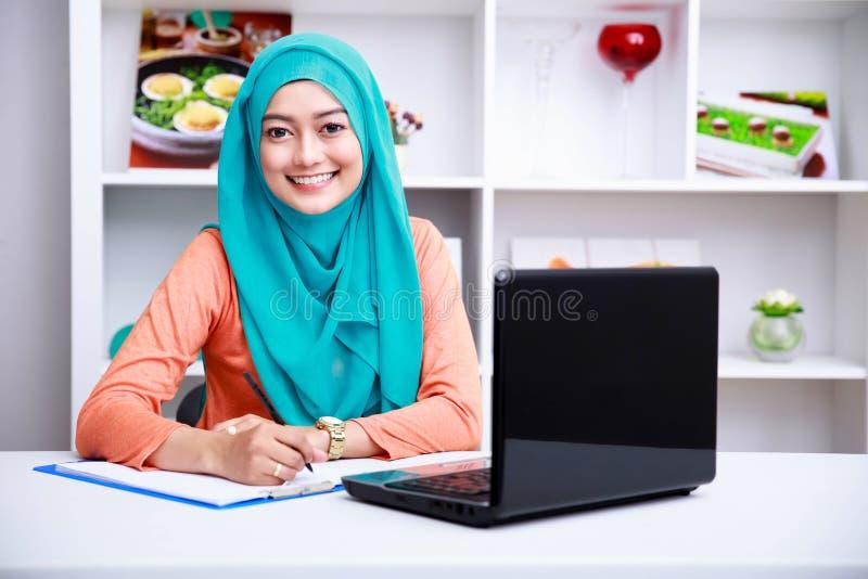 Härlig muslimkvinna som skriver en information från bärbara datorn arkivfoton