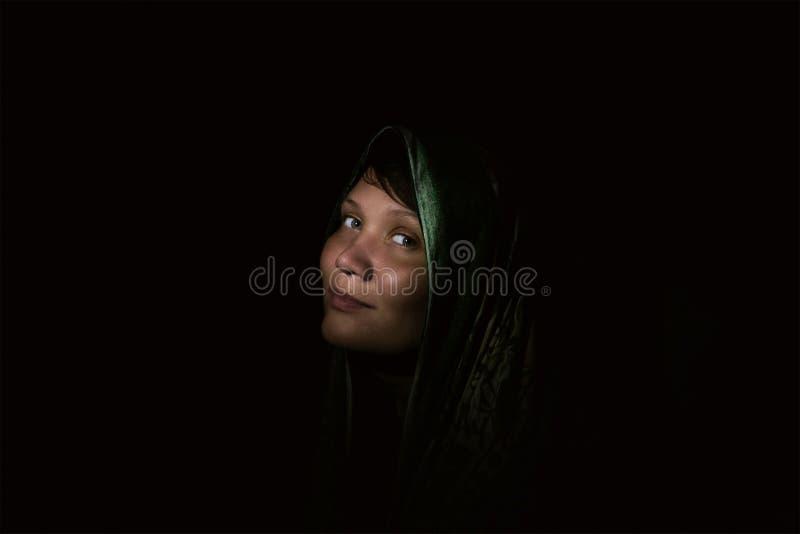 Härlig muslimsk ung kvinna i mörker Mörkt rum, det dunkla ljuset av ficklampan arkivfoton