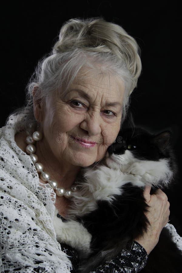 Härlig mycket gammal kvinna med en katt arkivbild