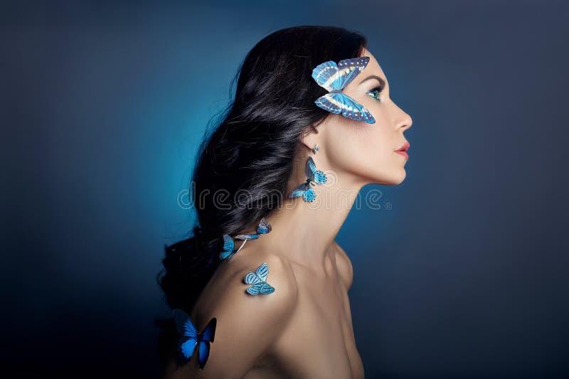 Härlig mystisk kvinna med blå färg för fjärilar på hennes framsida, brunett och pappers- konstgjorda blåa fjärilar på flickorna royaltyfri fotografi