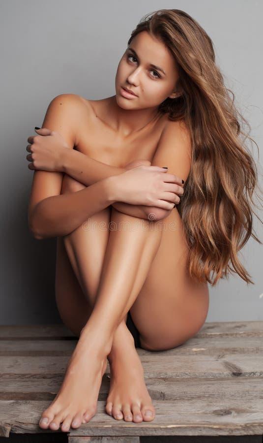 Härlig näck kvinna med perfekt hud på en bakgrund arkivfoto