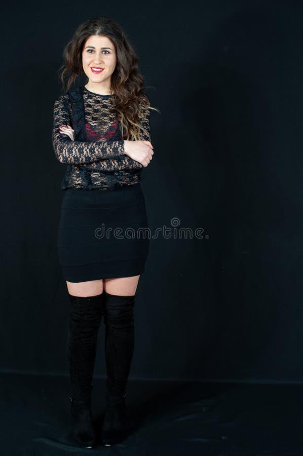 Härlig närbild av den tonåriga unga sinnliga brunetten Svärta kängor, svart mini- kjol med det svarta ingreppet som långa muffar  royaltyfri bild