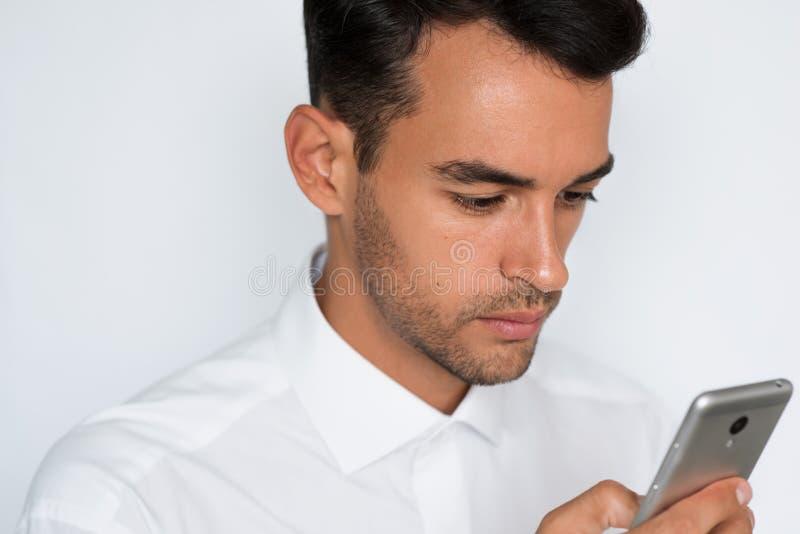 Härlig närbildstående av den unga mannen som använder mobiltelefonen på grå bakgrund Affärsman som talar på hans smarta telefon royaltyfri bild
