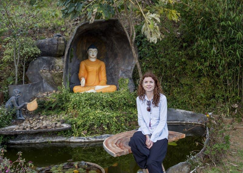 Härlig nätt kvinna som sitter på bänken nära statyn av Buddha fotografering för bildbyråer