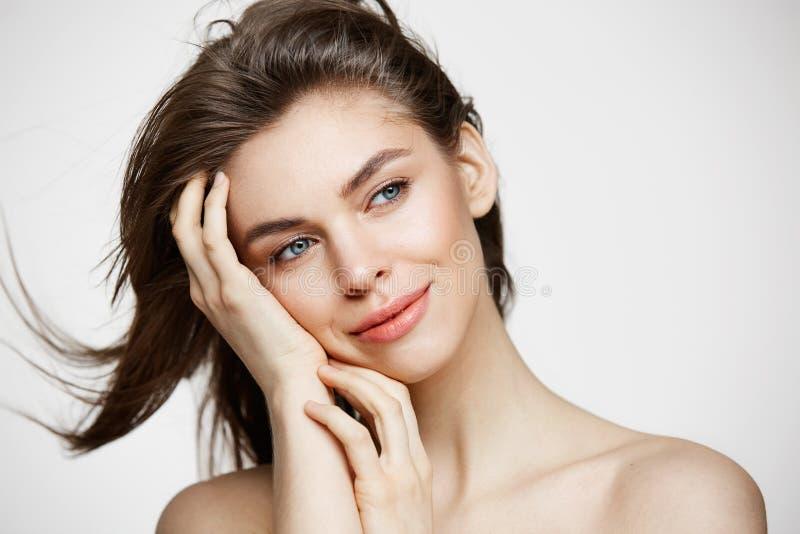 Härlig naken ung flicka med perfekt ren hud som ler rörande hår över den vita väggen Ansikts- behandling royaltyfri foto