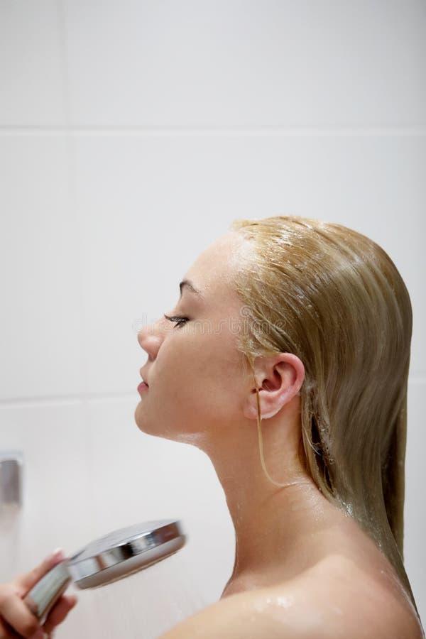 Härlig naken ung kvinna som tar duschen i badrum arkivfoton