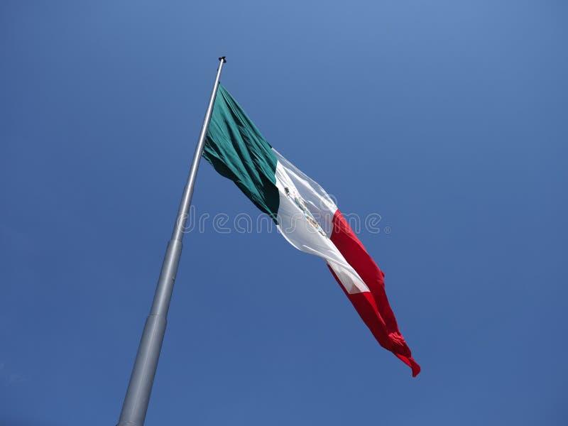 Härlig nationell maxican flagga på stranden på fjärden av Stilla havet i den Acapulco staden i Mexico med klar blå himmel royaltyfria bilder