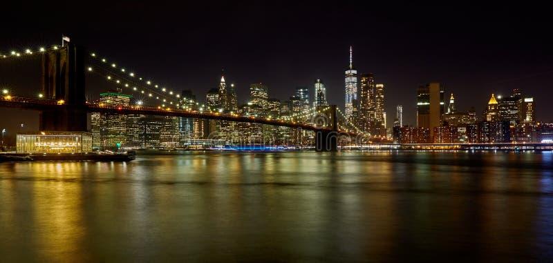 Härlig natthorisont av i stadens centrum New York med den Brooklyn bron i förgrunden royaltyfri bild