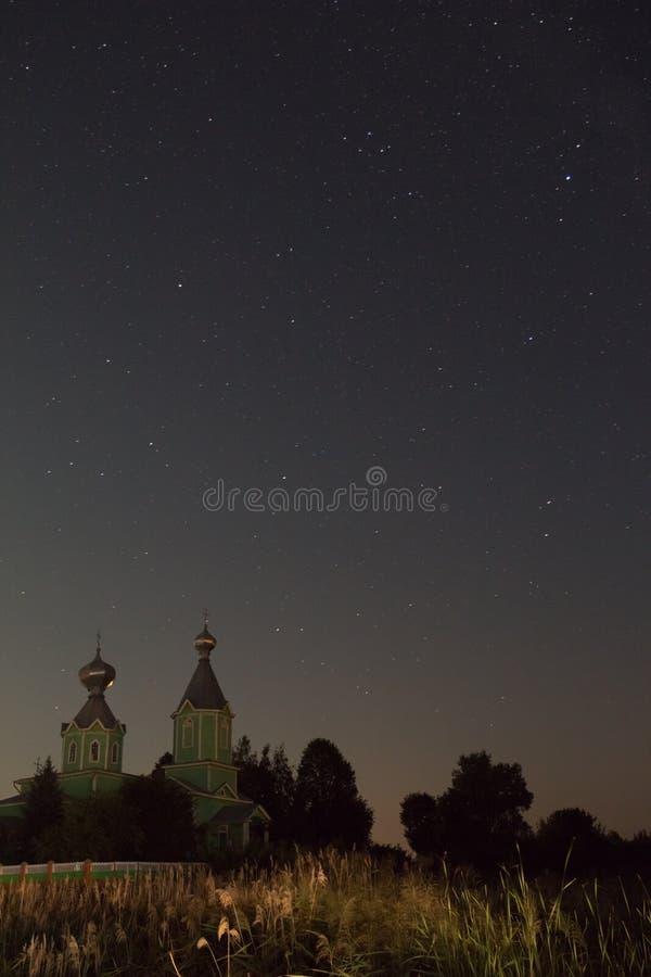 Härlig nattlandskapkyrka under den stjärnklara himlen arkivfoto