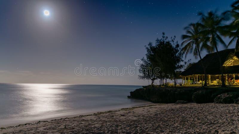 Härlig nattsikt av en a-paradisstrand med silverglöd av månsken som reflekterar av av vatten royaltyfri foto