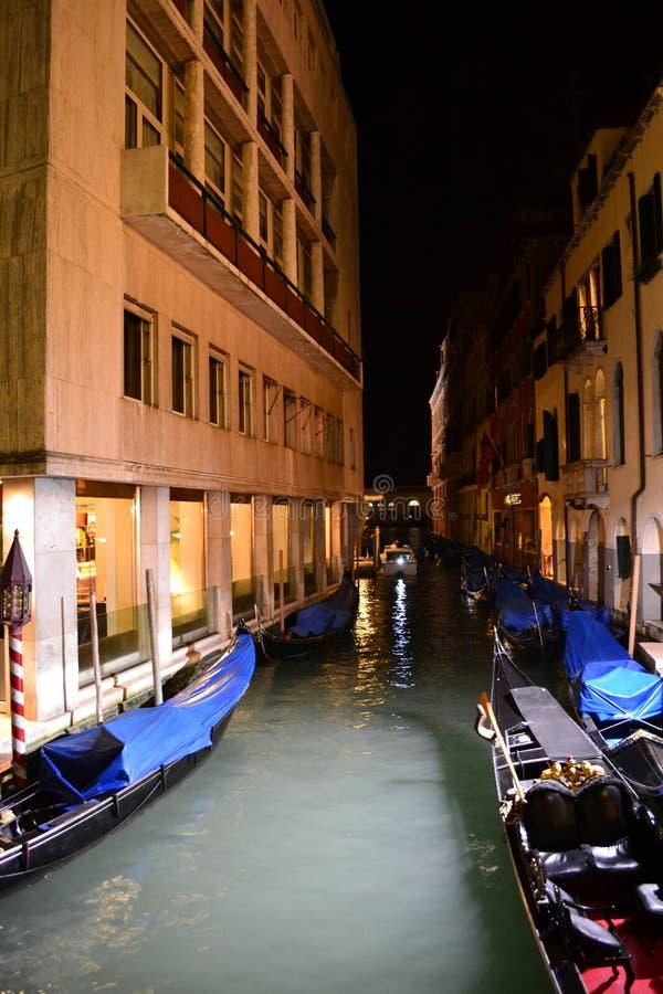 Härlig nattsikt till gondoler som ankras i en kanal arkivfoto