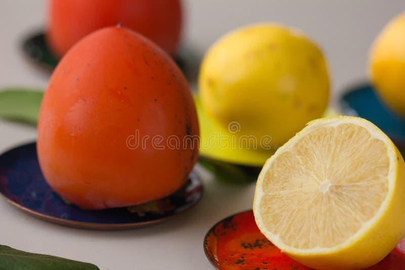 Härlig ny persimonfrukt mogen persimon på en träbakgrund Persimonsnitt in i stycken Närbild arkivfoton