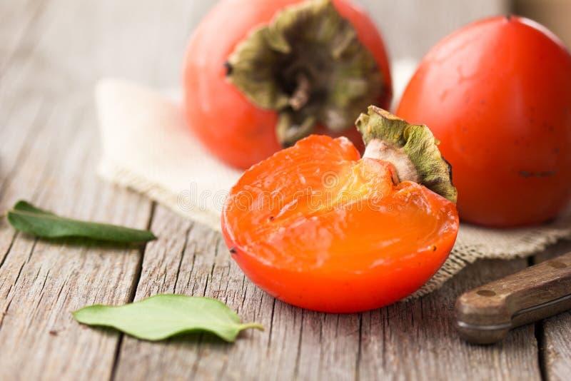 Härlig ny persimonfrukt mogen persimon på en träbakgrund Persimonsnitt in i stycken Närbild royaltyfri foto