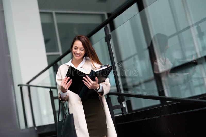 Härlig och attraktiv affärskvinna som ser mappar royaltyfri fotografi