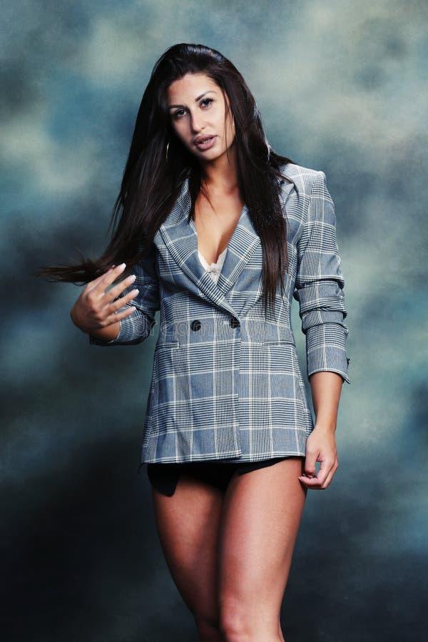 Härlig och attraktiv brunettflicka som poserar i studio royaltyfria foton