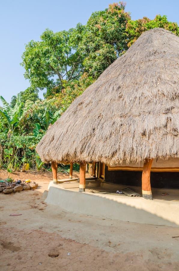 Härlig och färgrik traditionell halmtäckt rund gyttja och lera förlägga i barack i lantlig by av Guinea Bissau, Västafrika arkivbild