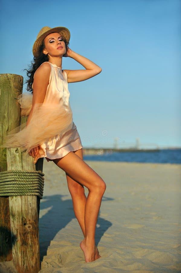 Härlig och för mode ung kvinna med långa ben i lyxig klänning och hatt royaltyfria bilder
