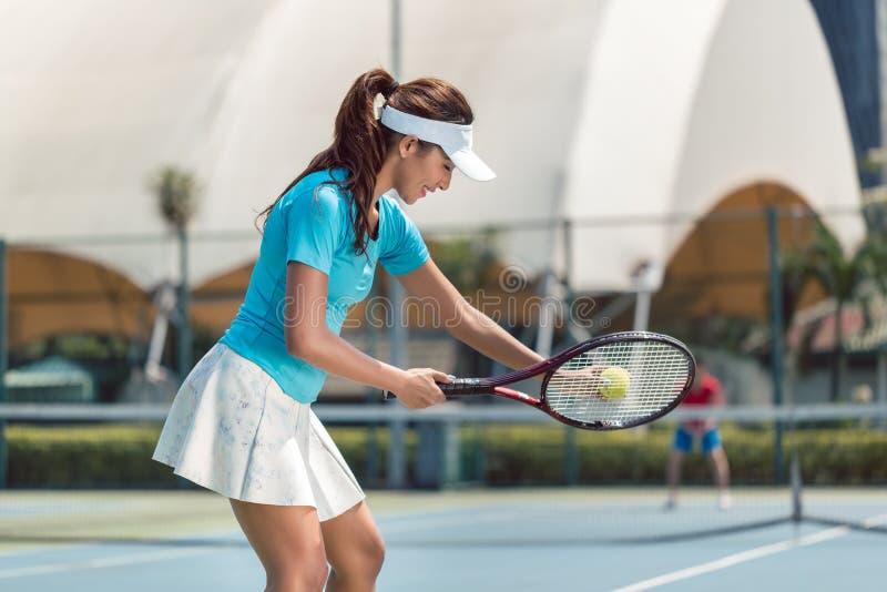 Härlig och konkurrenskraftig kvinna som ler, innan att starta en tennismatch royaltyfri fotografi