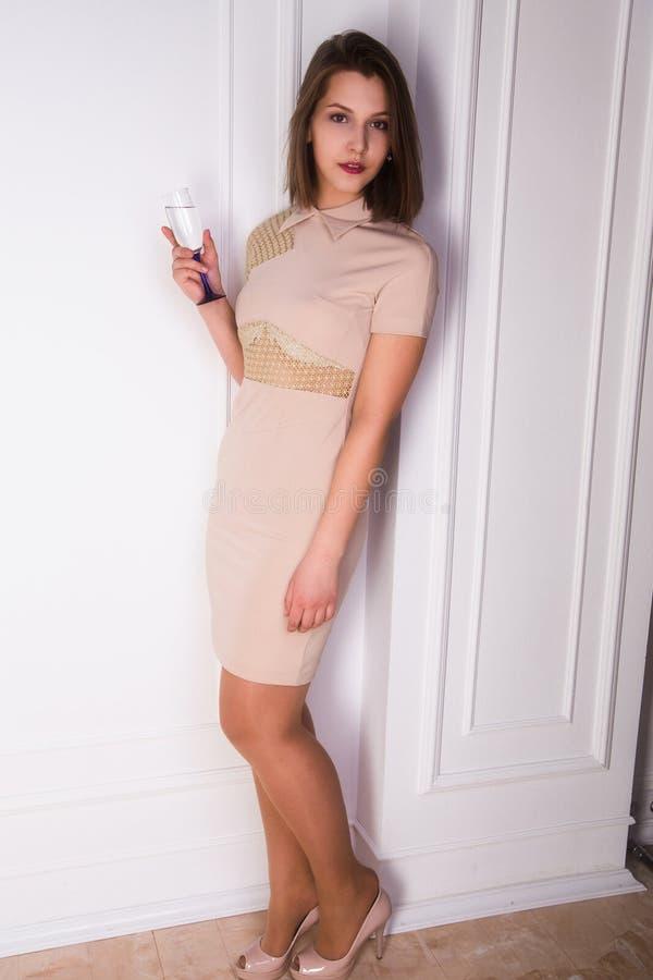 Härlig och lycklig ung flicka i en elegant klänning arkivfoto