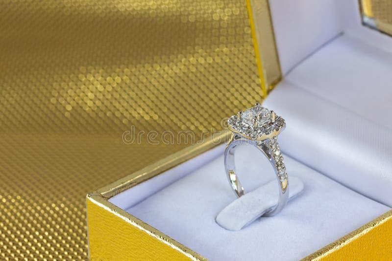 Härlig och lyxig gåva för bröllop för diamantcirkel i ask på guld- bakgrund arkivbilder