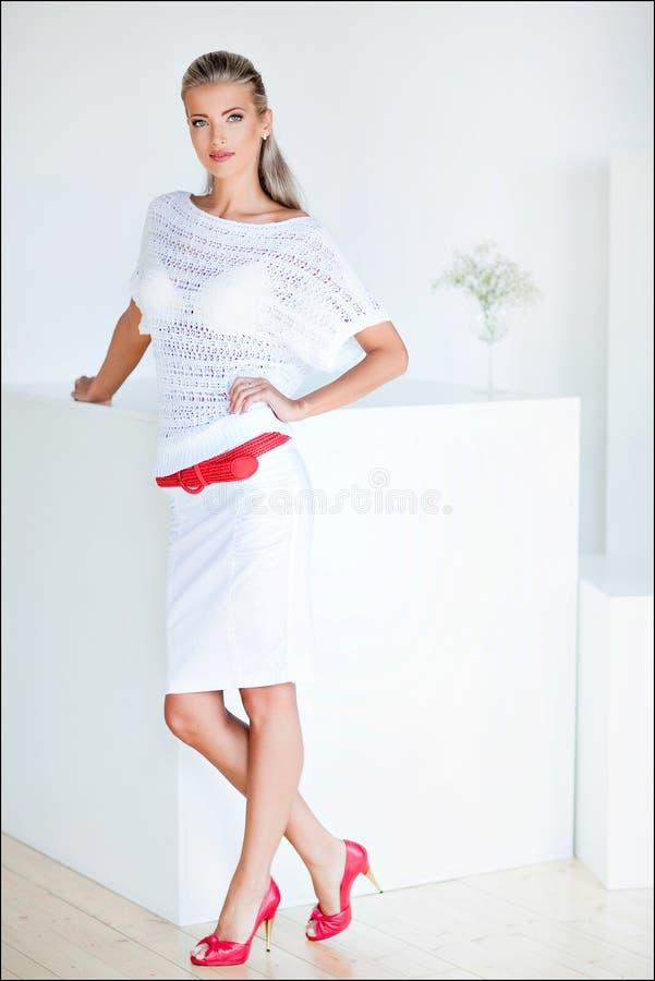 Härlig och sinnlig blond flicka i ett vitt klänninganseende på t royaltyfri fotografi
