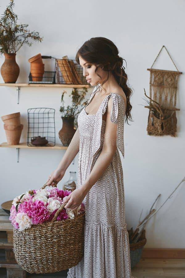 Härlig och sinnlig brunettmodellflicka, med fulla sexiga kanter och med korgen av blommor i hennes händer, i lång klänning arkivbilder