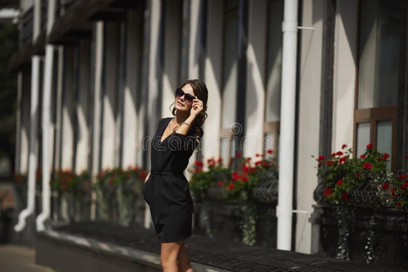 Härlig och trendig modellflicka med ett skinande leende i en stilfull svart kort klänning och i solglasögon som förbi går royaltyfria foton