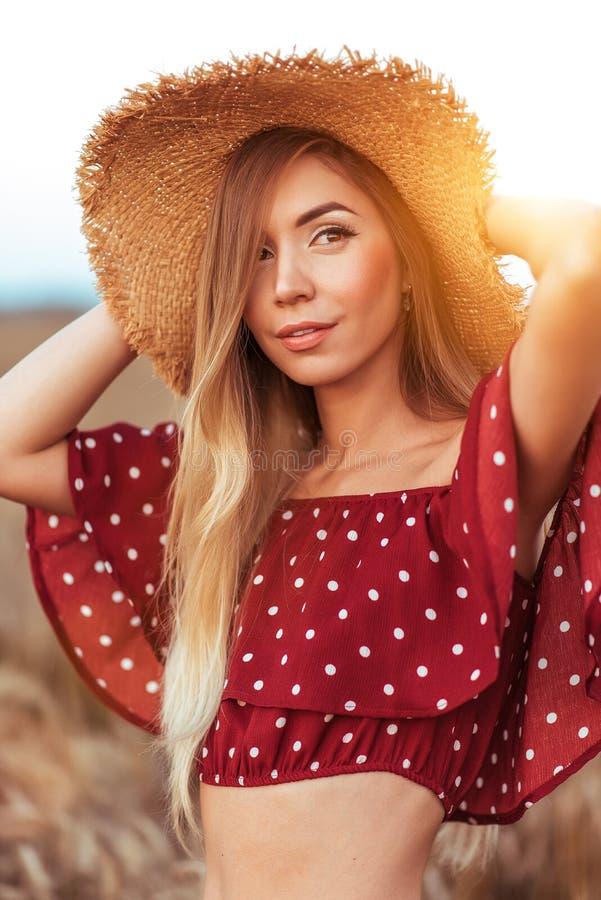 Härlig och ung kvinna i en sugrörhatt, i sommar i ett fält, en röd klänning, ett långt idrotts- hår och ett brunbränt diagram arkivfoton