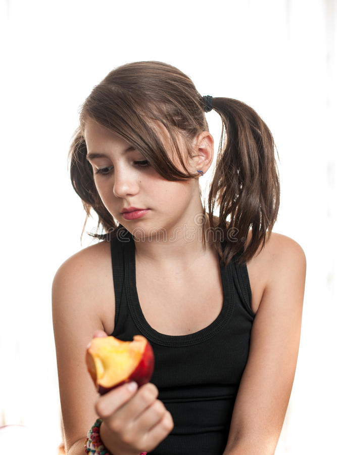 Härlig och ung tonårs- flicka i svart t-skjorta som äter en persika arkivfoto