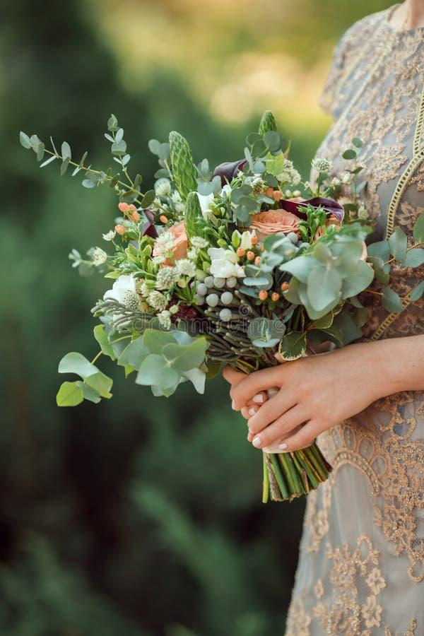 Härlig original- bröllopbukett i brudhänderna royaltyfria foton