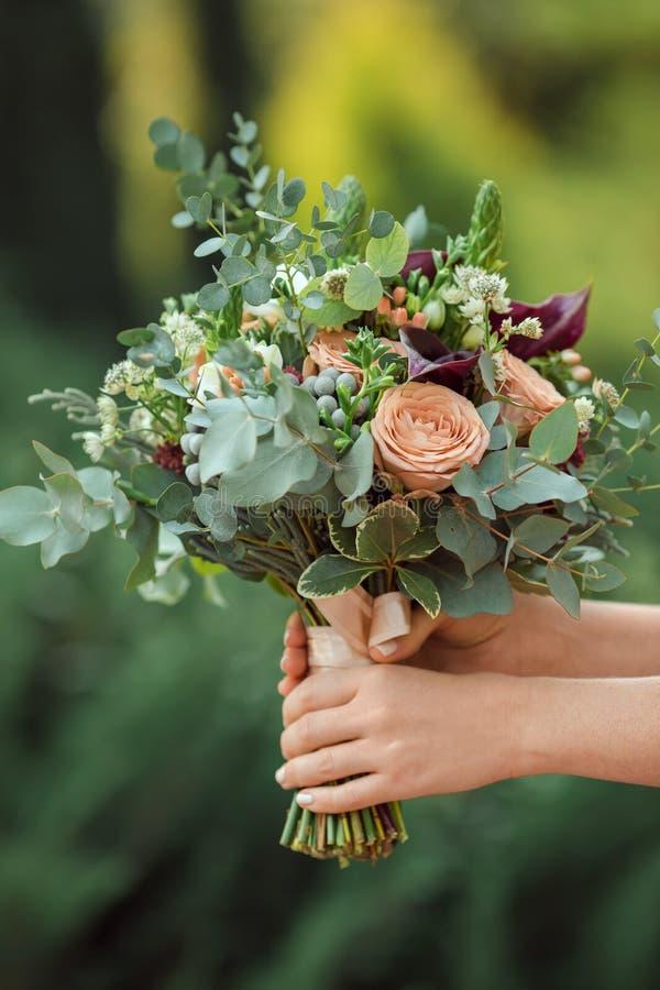 Härlig original- bröllopbukett i brudhänderna royaltyfri bild
