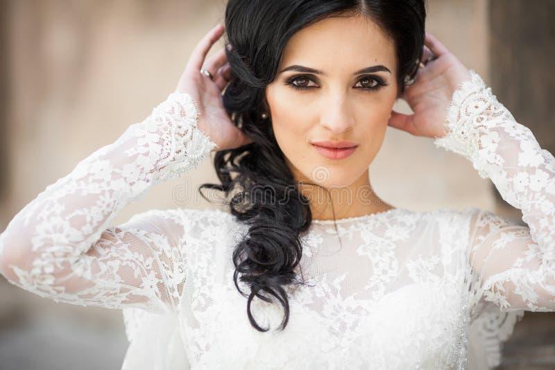 Härlig oskyldig brunettbrud i den vita klänningen som poserar nära chu royaltyfri fotografi