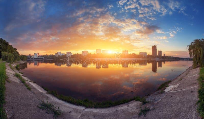 Härlig panorama- cityscape på solnedgången mot bakgrund field blåa oklarheter för grön vitt wispy natursky för gräs royaltyfria foton