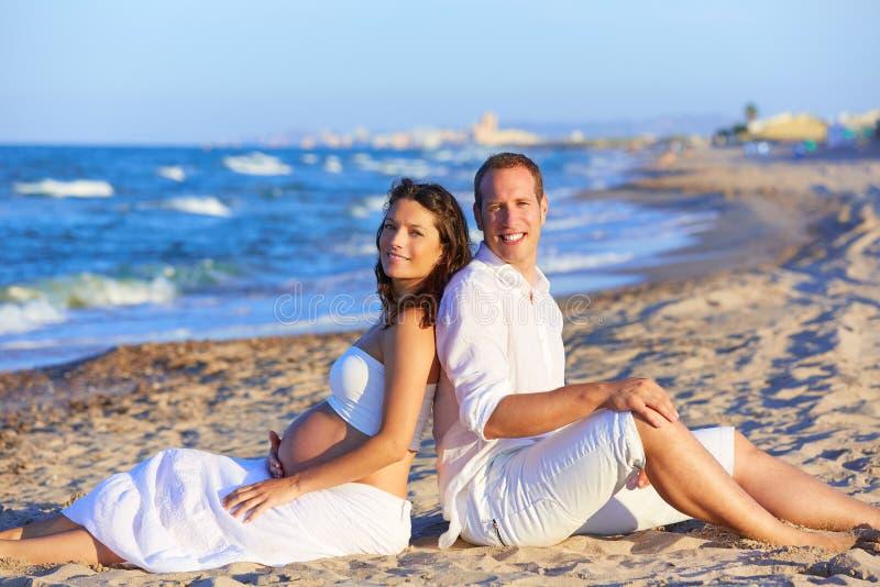 Härlig pargravid kvinna i stranden fotografering för bildbyråer