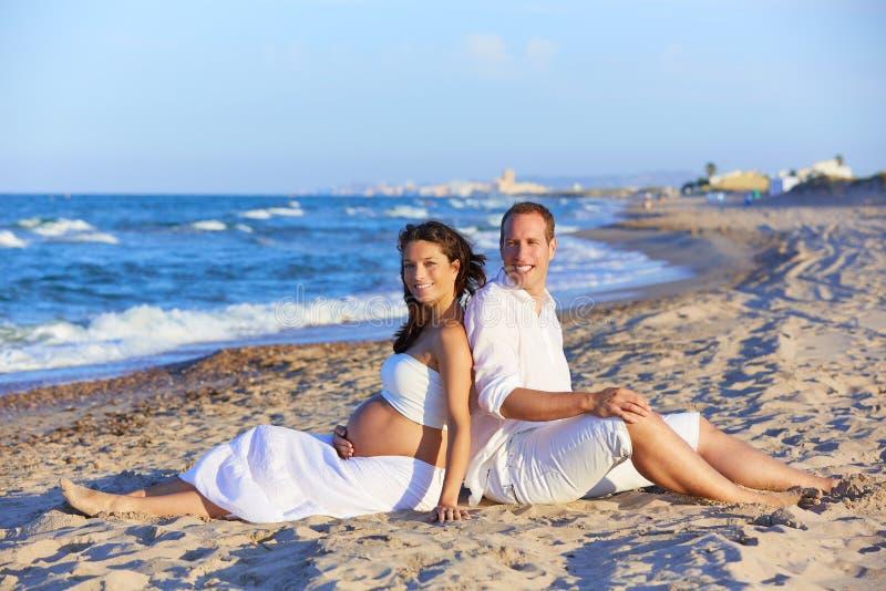 Härlig pargravid kvinna i stranden royaltyfri foto