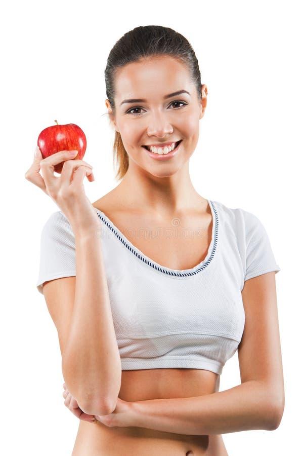 Härlig passformkvinna som rymmer ett äpple arkivfoton