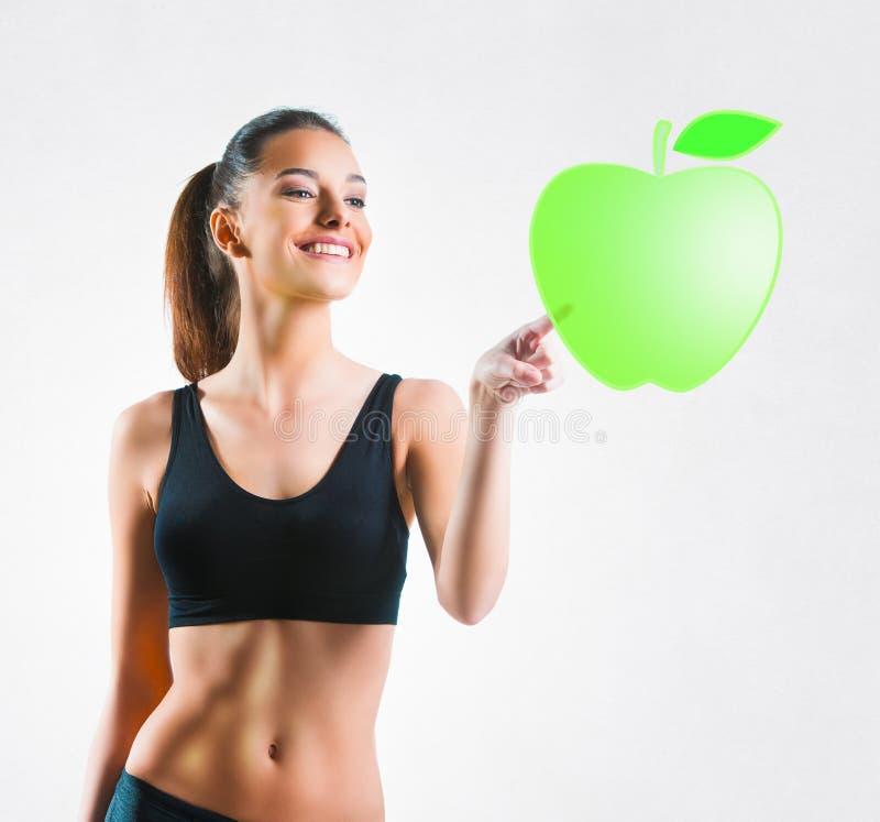 Härlig passformkvinna som trycker på ett äpplesymbol arkivbild